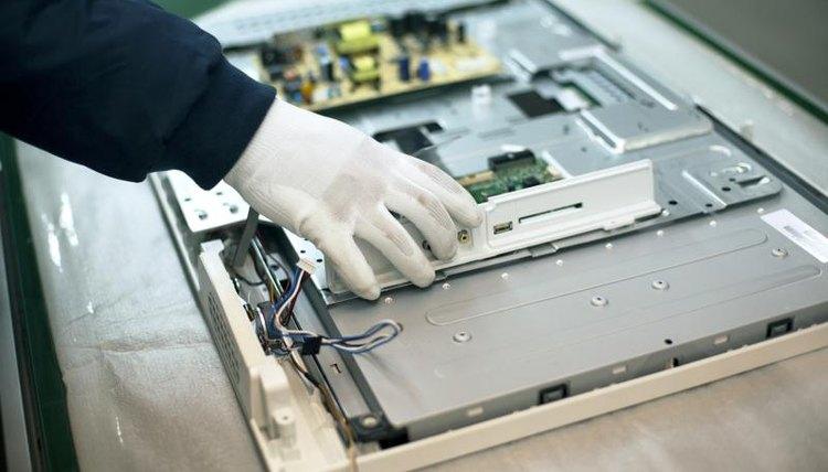 A technician assembles a components of a flatscreen television