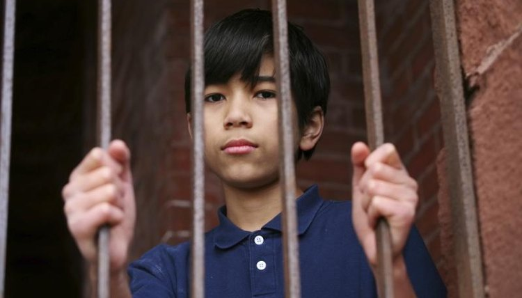 Child standing behind bars