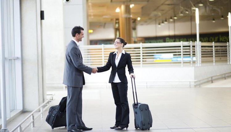 Two businesspeople shaking hands at an airport.