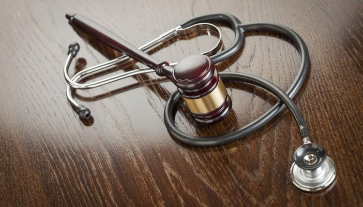 A gavel and stethoscope on a table.