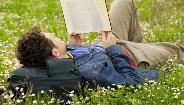 Teenager reading book in grass field