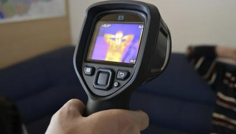 A man looks at a thermograph of himself.