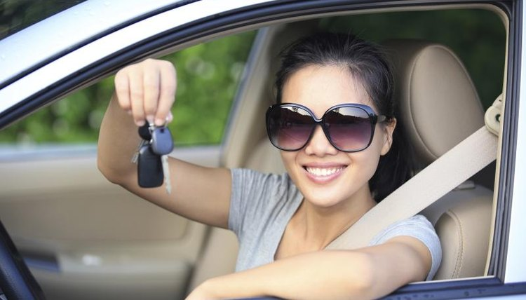 A happy woman in the drivers seat holding the keys to her new car.