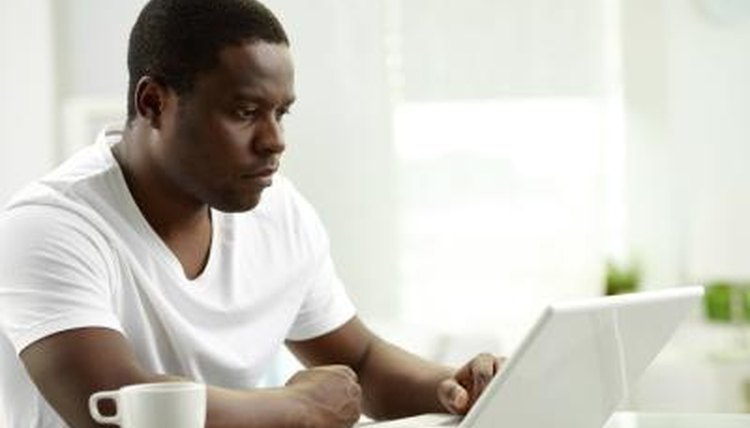 Student typing essay up at home on laptop