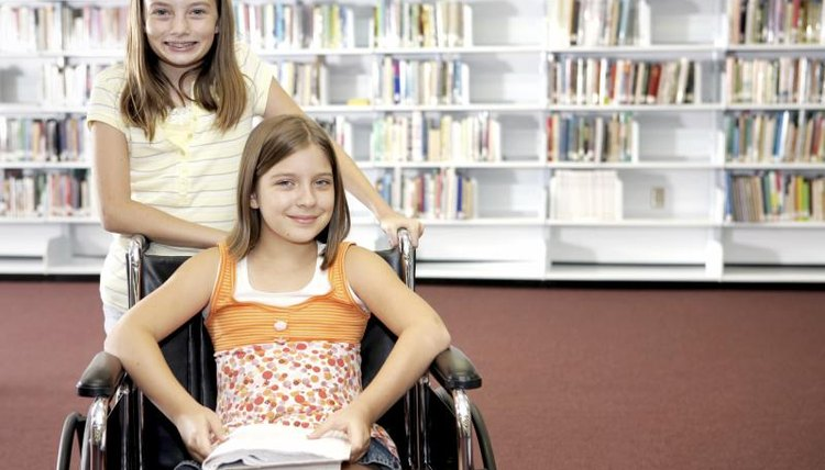 Student helping another student in a wheelchair in the school library.