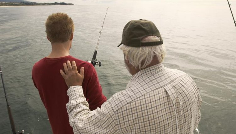 A father and son fishing together off a boat.