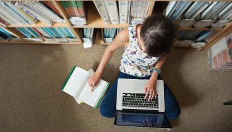 Student using laptop on floor of library