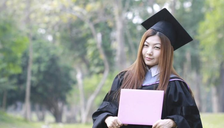 A woman is standing with her diploma while wearing her cap and gown.