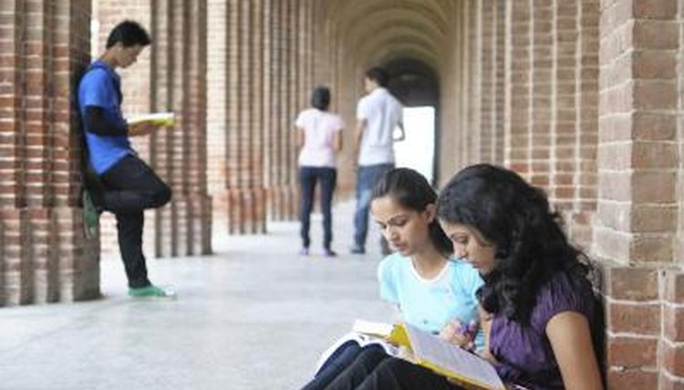 Students studying in outdoor university corridor
