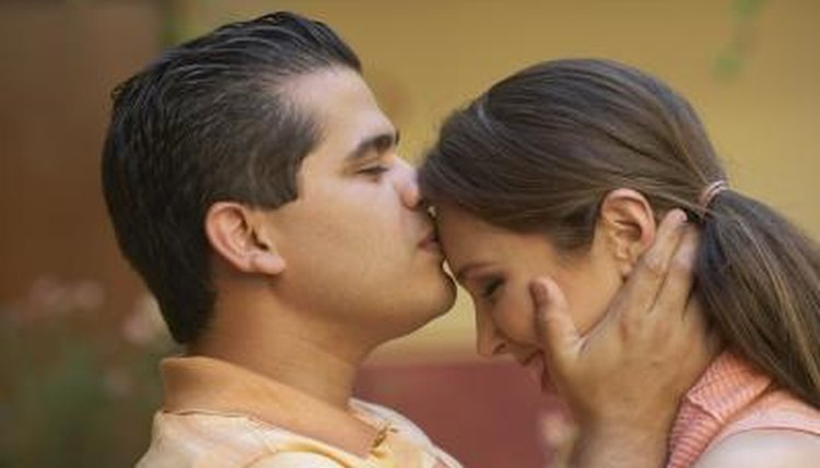 Man kissing woman on forehead