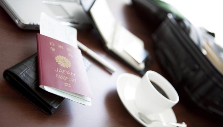 A passport sitting on a table by a cup of coffee.