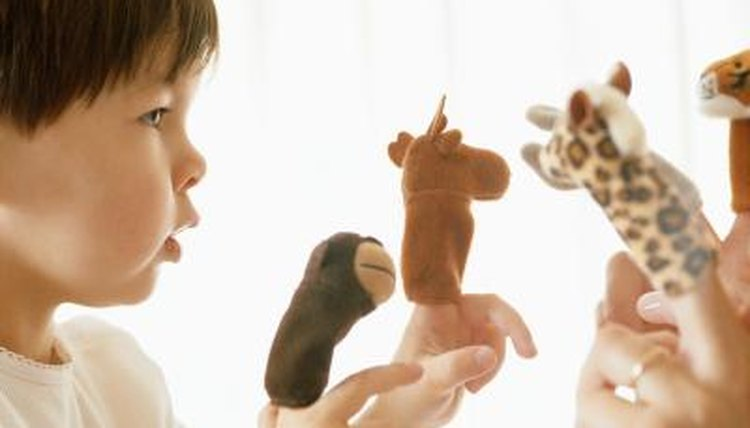 Young child playing with finger puppets.