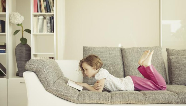 Child reading book on couch.