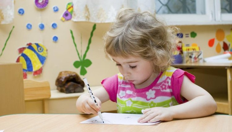 Preschooler coloring at desk.