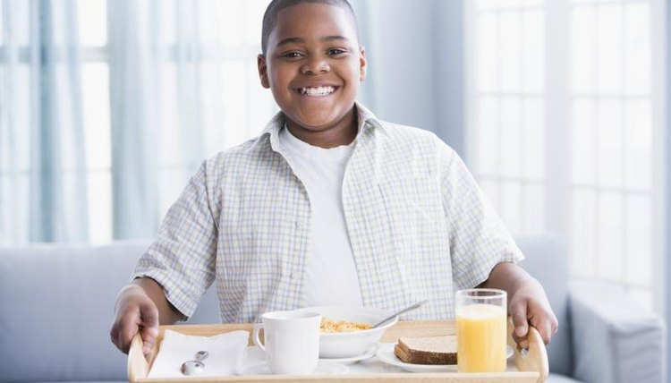Young boy holding up a breakfast tray.