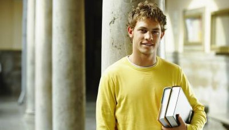 Student holding books on campus.