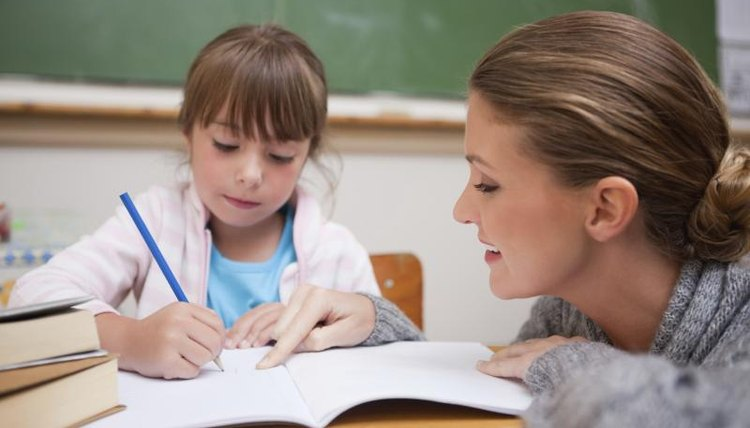Elementary school teacher working with young student