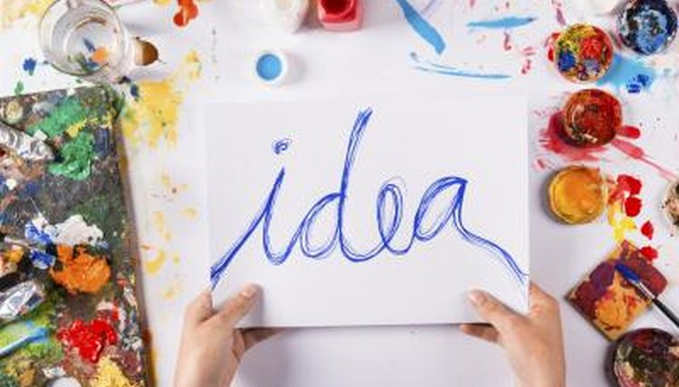 "A person paints the word ""idea"" onto a piece of paper."