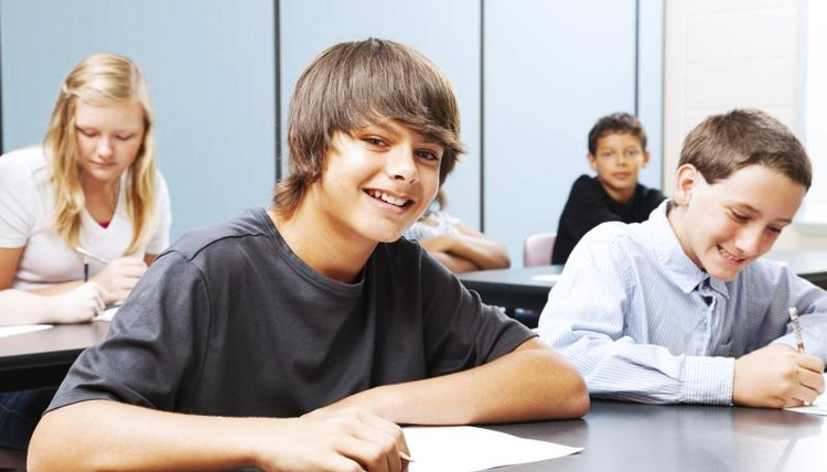 Smiling middle school students sitting at tables