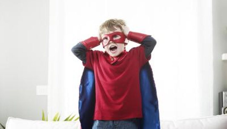 Child dressed up as a superhero with cape and mask