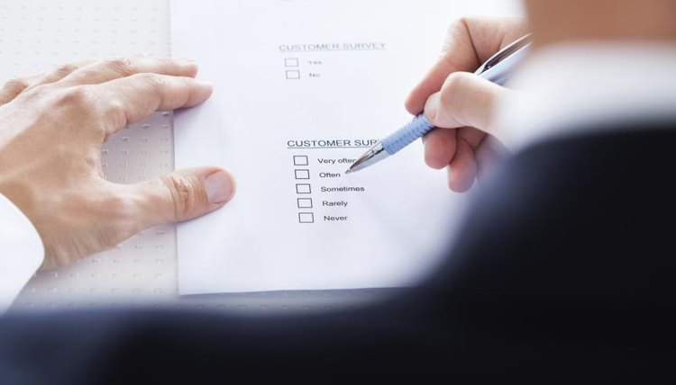 A man is filling out an evaluation form.