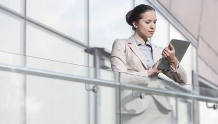 A young business woman is using a tablet at work.