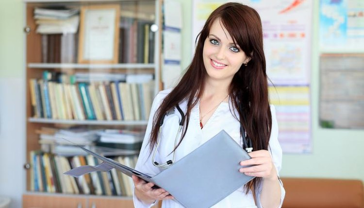 Smiling young medical assistant holding binder in office