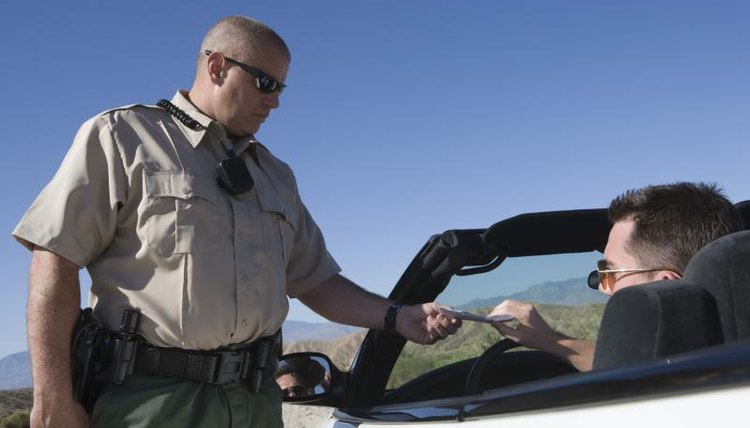 Police officer handing a convertible driver a traffic ticket.