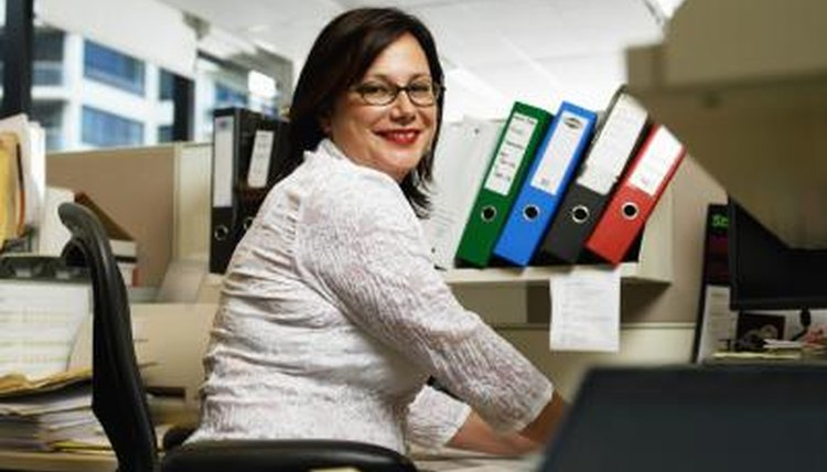 A woman compiling paperwork smiling at her desk.