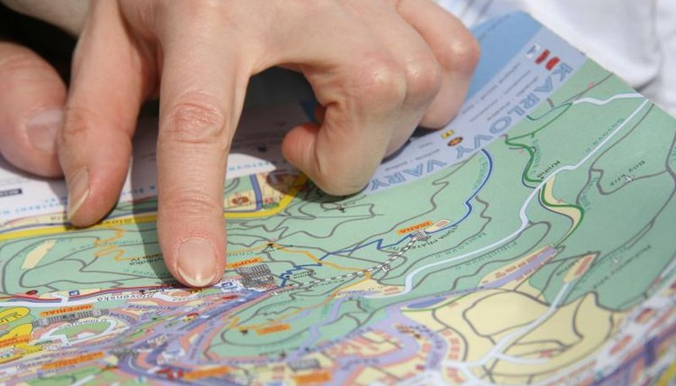 Close-up of hand pointing to map
