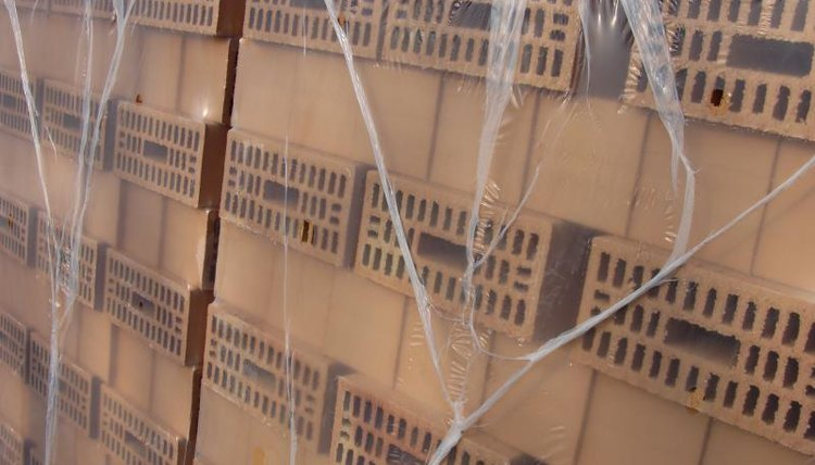 Stacks of bricks wrapped in plastic sheeting
