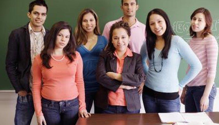 Teacher standing beside students in classroom.