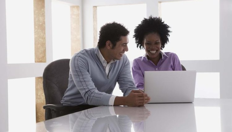 Man and woman working on laptop together at table.