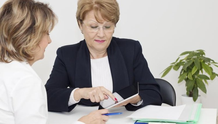 A senior woman is meeting with an advisor in her office.