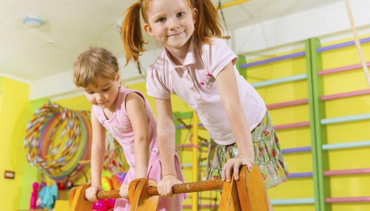 Children playing with preschool gymnastic obstacles.