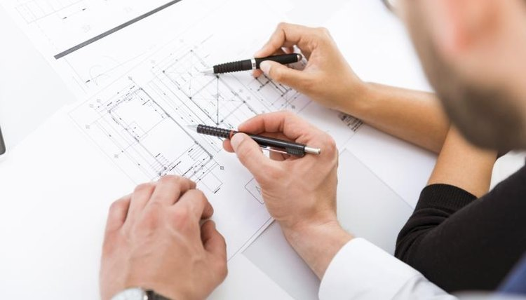 Close-up of two architecture students drawing on draft paper