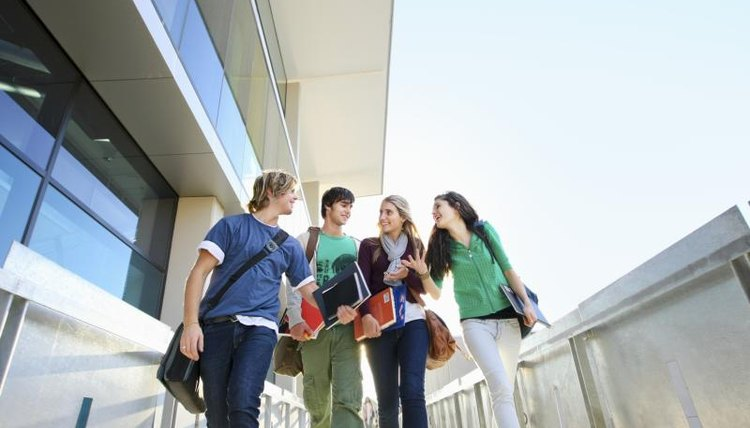 Students walking in front of a building on a college campus.