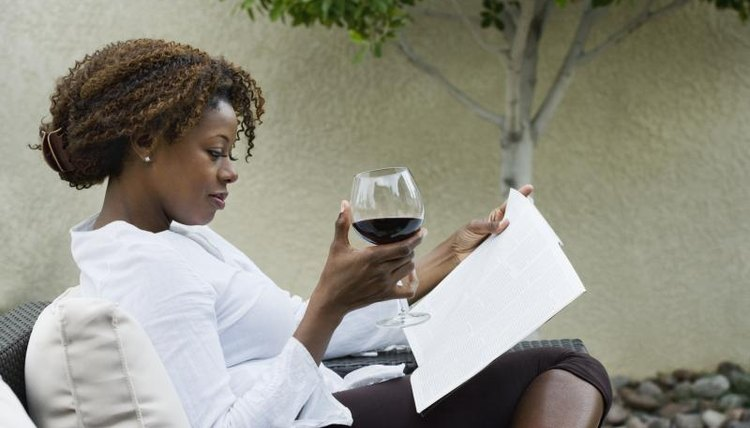 Woman reading book on porch with glass of wine.