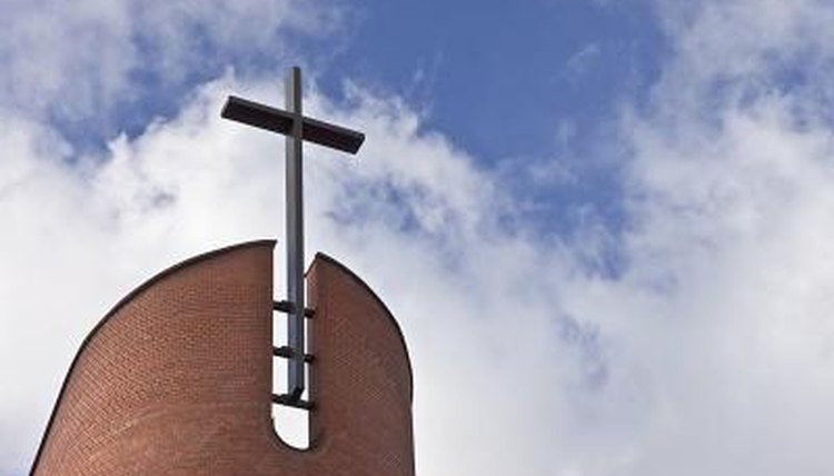 Cross on church roof against sky with clouds
