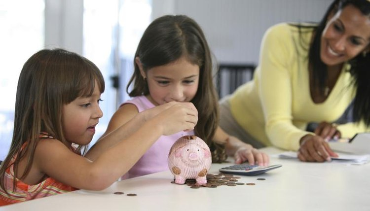 Young children putting coins in piggy bank