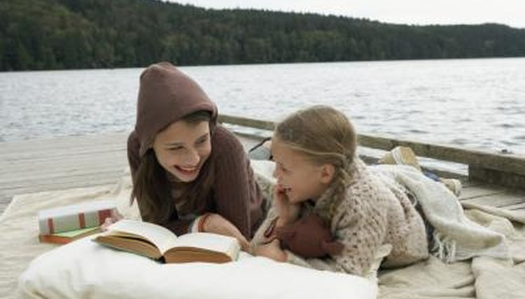 Two young girls are reading outside.