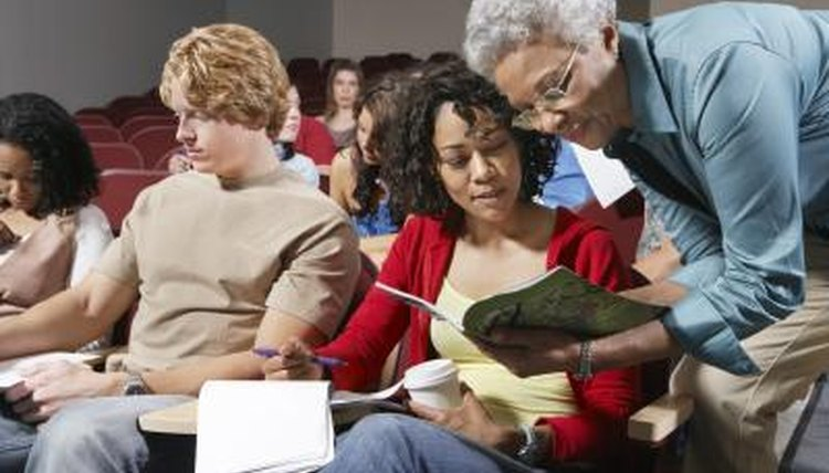 Professor showing course catalog to student in lecture hall