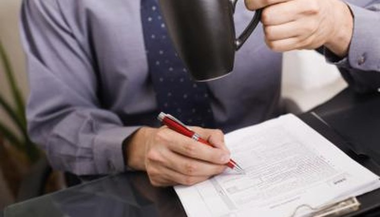 Image of man signing a document.