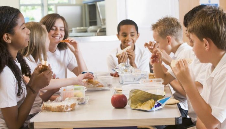 School children eating lunch in the cafeteria.