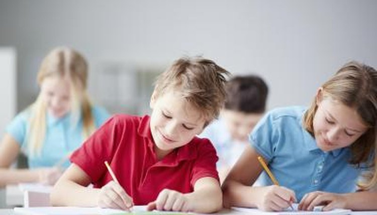 Two students writing in notebooks in elementary school.