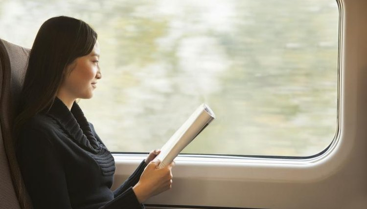 Student reading periodical on train.