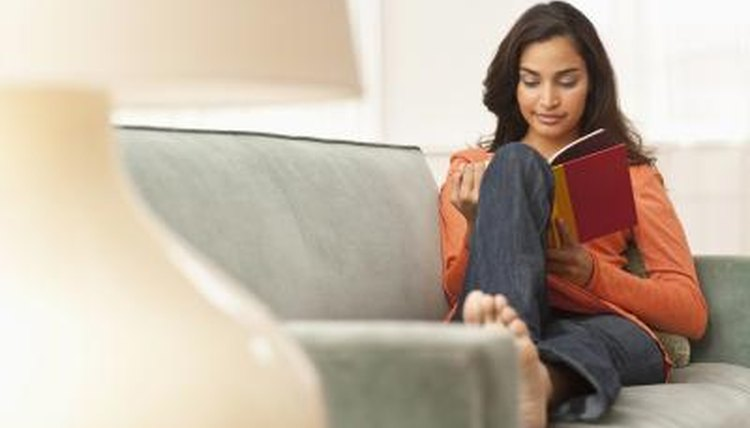 Woman reading book on couch.