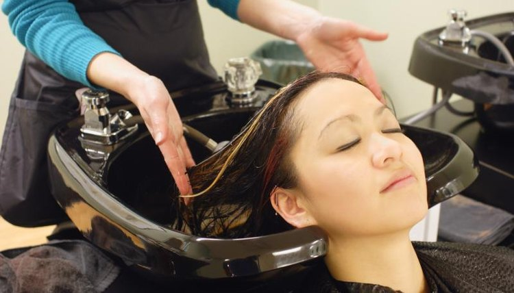Woman getting hair washed at Aveda Institute
