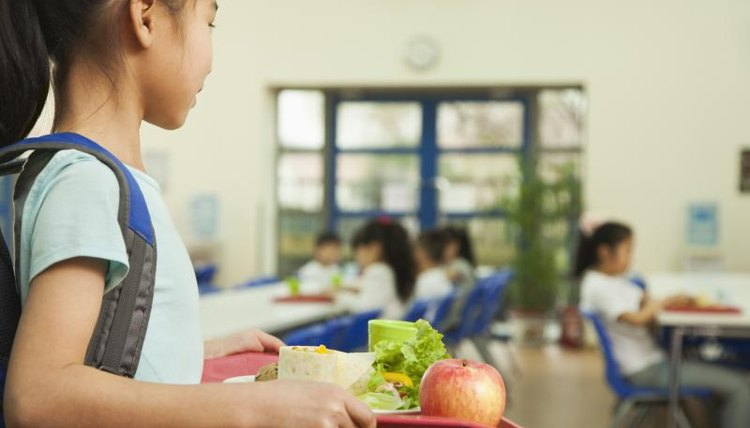 A young girl is walking in the lunch room.