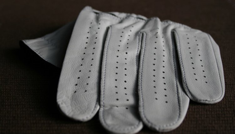 The golf glove makes holding onto the club easier.